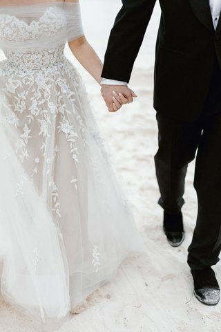 wedding-couple-bride-and-groom-walking-on-beach-tuxedo-formal-gown-tulle-wrap-floral-appliques