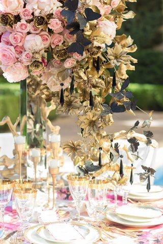 large-overflowing-floral-centerpiece-with-floral-linens-and-gold-details-on-plates-and-glasses