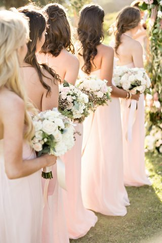 bridesmaids-pink-dresses-lined-up-bouquets-white-pink-flowers-greenery-chiffon-fabric-wedding