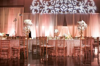 wedding-reception-with-peach-draping-rosette-tablecloths-and-golden-chairs