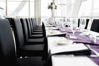 wedding-reception-light-bright-venue-with-long-table-purple-linen-black-chairs-high-centerpiece