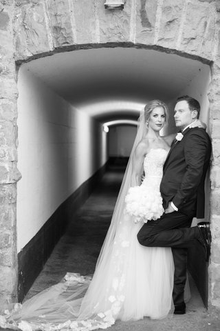 black-and-white-photo-of-bride-and-groom-in-hallway-archway-bride-in-strapless-gown-groom-in-tuxedo