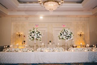 two-flower-centerpieces-on-top-of-long-reception-table