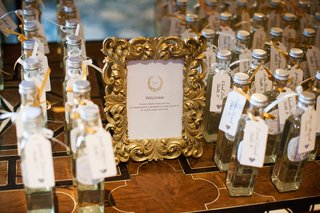 escort-cards-attached-to-homemade-limoncello-bottles-gold-frame-ornate-with-sign