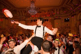 groomsmen-lifting-groom-in-chair-during-hora-at-wedding-reception-at-the-plaza