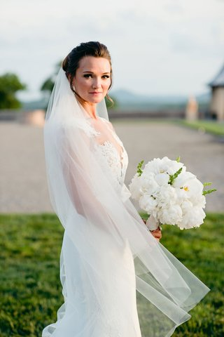 bride-in-lace-wedding-dress-illusion-neckline-in-veil-with-white-peony-flower-bouquet-orchid