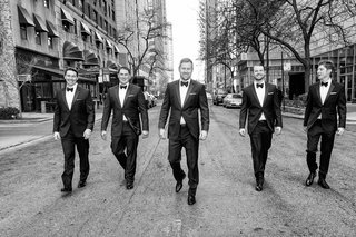 black-and-white-photo-of-groom-and-groomsmen-in-tuxedos-and-bow-ties-walking-down-chicago-street