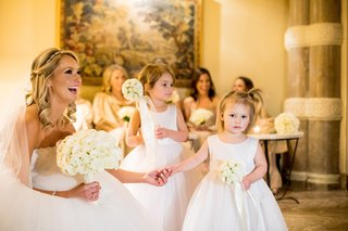 bride-in-monique-lhuillier-ball-gown-holds-hand-of-flower-girl-with-pomador
