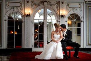 groom-kisses-brides-shoulder-while-sitting-on-red-bench