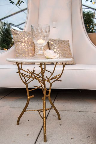 accent-table-with-gold-branches-at-base-around-white-settee-at-cocktail-hour