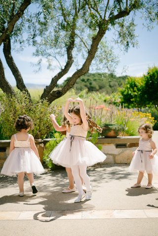 flower-girls-in-blush-dresses-and-silver-ribbons-dance-and-do-ballet-twirls