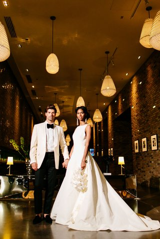 bride-in-inbal-dror-ball-gown-orchid-bouquet-groom-in-white-tuxedo-jacket-warmly-lit-hallway