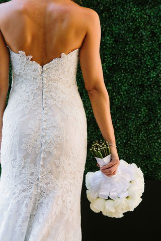 bride-in-a-strapless-alencon-lace-dress-holds-bouquet-of-white-roses-ribbon