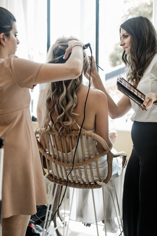 bride-in-pretty-slip-dress-long-curled-hair-getting-glam-with-hairstylist-and-makeup-artist