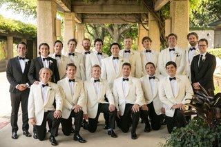 groom-and-groomsmen-ivory-white-tuxedo-jackets-attendants-in-black-white-classic-tuxedos