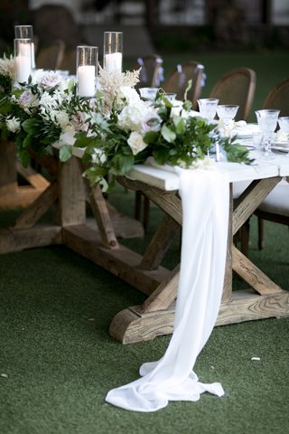 wooden-head-table-with-soft-fabric-runner-and-garland-of-greenery-and-flowers-pillar-candles