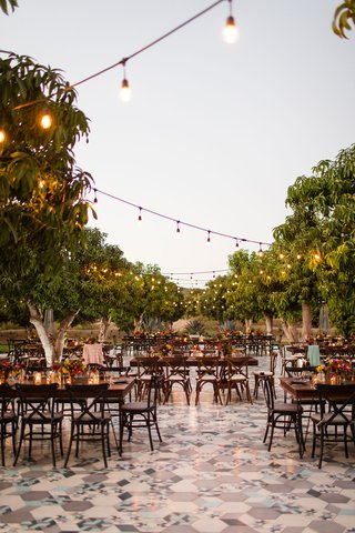 dark-wood-tables-and-chairs-with-trees-bistro-lights-courtyard-wedding-reception-unique-tile