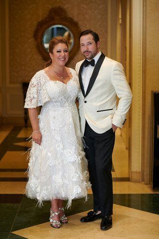 bride-in-feathered-stephen-yearick-reception-dress-groom-in-white-tuxedo-jacket