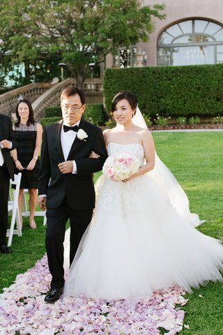 bride-and-father-walk-down-aisle-covered-with-layer-of-pink-and-purple-petals