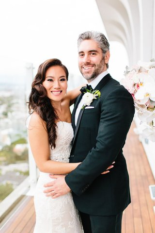 bride-in-wedding-dress-hugging-groom-in-tuxedo-boutonniere-on-balcony-of-mr-c-beverly-hills