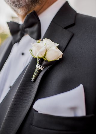 boutonniere-with-three-white-roses-wrapped-with-pearl-beading-and-gold-detailed-black-ribbon