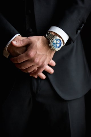 groom-in-black-tuxedo-wears-breitling-watch-with-a-dark-blue-face