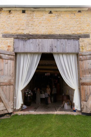 iowa-barn-wedding-ceremony-entrance-with-drapes-and-wood-doors