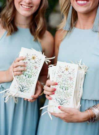 honor-attendants-in-blue-dresses-holding-ceremony-program-flower-print-vintage-design-with-ribbon