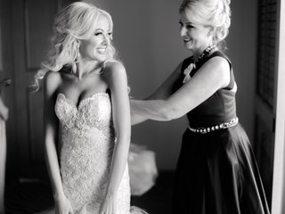 black-and-white-photo-of-bride-smiling-in-strapless-wedding-dress-at-mom-helping-her-button-the-back