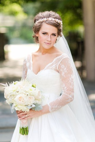 bride-in-white-wedding-dress-with-lace-three-quarter-sleeves-and-v-neck-with-white-bouquet