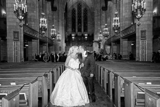 black-and-white-photo-of-bride-in-an-ines-di-santo-gown-kissing-groom-in-black-tux-in-church-aisle