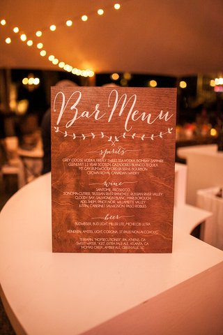 wood-sign-with-bar-menu-in-calligraphy-spirits-wine-beer-selections-at-wedding-reception