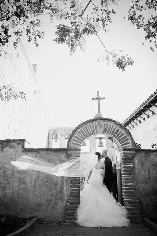 black-and-white-photo-of-bride-in-romona-keveza-kisses-groom-at-mission-san-juan-capistrano