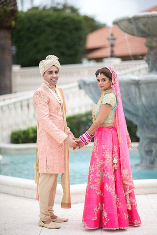 indian-american-bride-and-groom-in-traditional-wedding-attire-during-first-look-lengha-sherwani