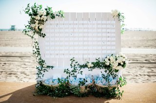 beachside-wedding-reception-with-clapboard-place-card-display-greenery-white-roses-flip-flops