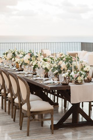 wedding-reception-on-rooftop-outdoors-cabo-mexico-wood-table-round-back-french-chair-low-centerpiece