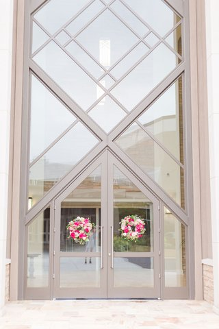 wedding-ceremony-tall-church-doors-windows-white-and-pink-flowers-greenery