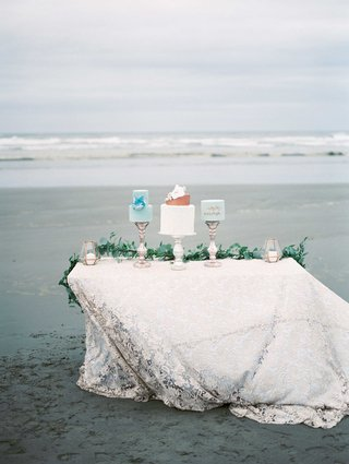 three-different-cakes-on-top-of-a-white-linen-table-with-a-green-garland-runner-on-a-beach