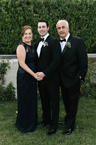 mother-of-groom-in-sleeveless-black-long-gown-dress-with-lace-neckline-groom-and-father-in-tuxedos
