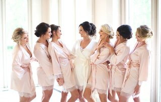 bride-in-white-satin-robe-and-bridesmaids-in-blush-robes-lace-trim-updo-hairstyles