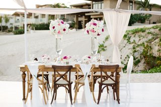 wood-table-and-chairs-with-fabric-backs-and-tall-arrangements-of-flowers-in-blush-hot-pink-and-white