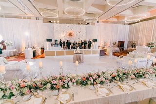 white-dance-floor-with-head-table-on-one-side-white-lounge-furniture-band-stage-with-backdrop