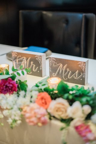 wedding-reception-sweetheart-table-with-mr-and-mrs-signs-white-rose-pink-flower-orange-greenery