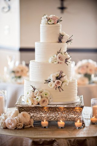 white-wedding-cake-ribbed-frosting-buttercream-with-clusters-of-fresh-ranunculus-rose-purple-foliage