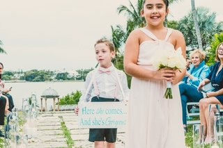 junior-bridesmaid-with-small-bouquet-ring-bearer-with-shorts-suspenders-and-bow-tie-carrying-sign
