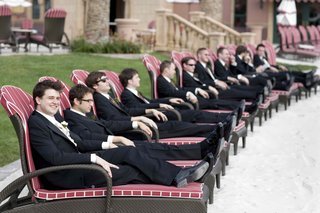 men-in-tuxedos-relaxing-on-pool-chairs