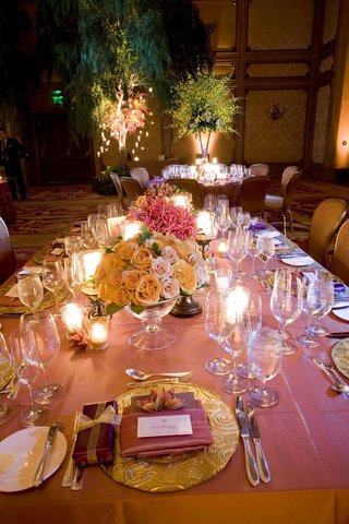 rectangular-table-topped-with-roses-and-gold-plates