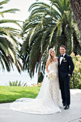 bride-in-ines-di-santo-lace-wedding-dress-long-train-and-veil-soft-bouquet-blonde-hair-groom-in-tux