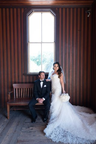 groom-on-bench-in-tuxedo-in-barn-and-bride-in-strapless-mermaid-wedding-dress-white-peony-bouquet