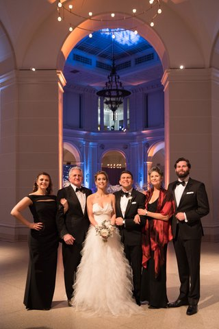 bride-and-groom-with-family-mother-in-black-dress-with-red-shawl-black-tie-wedding